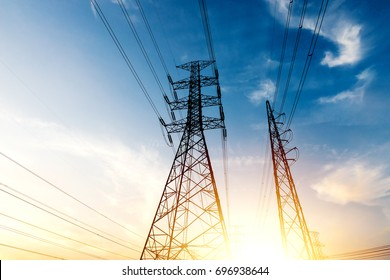 The silhouette of the evening electricity transmission pylon with sun