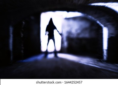 Silhouette of evil theatening body in dark basement - Sinister figure standing at dungeon door with dangerous attitude - Concept of a dreadful encounter with blurred subject in backlight - Image