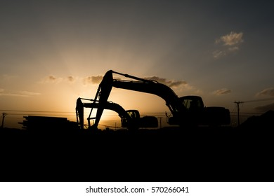 Silhouette of excavator at construction site in oilfield - sunset golden hour