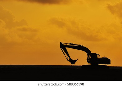 silhouette of Excavator loader at construction site with raised bucket over sunset.Heavy construction equipment for building truck digger crane bagger mix. Transportation