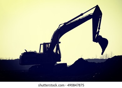 Silhouette excavator on construction site