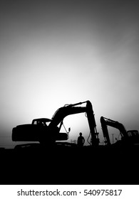 Silhouette of excavator and worker  at construction site in oilfield - sunset - black and white