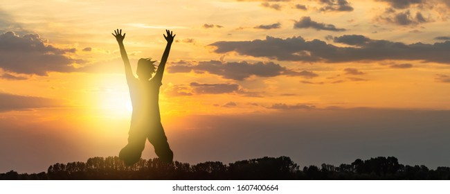 silhouette of an exuberant jump in the air, shiny sunset backgound with tree silhouette