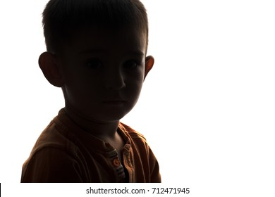 silhouette of the face of an unknowable little sad boy with protruding ears on a white isolated background