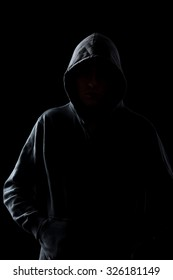 Silhouette of faceless guy in hoodie in the darkness, concepts of danger, crime, terror