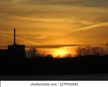 Silhouette of factory chimney and trees at sunset in Southern Denmark
