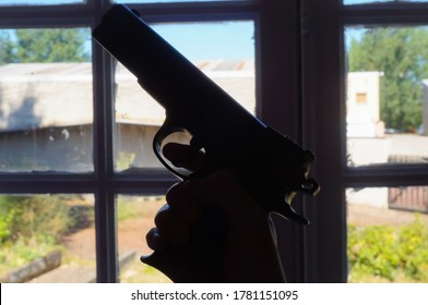 Silhouette of a fake but realistic gun (children's toy pistol) featuring a black plastic body held by a male hand with the finger on the trigger and pointed upwards in front of a multi-paned window