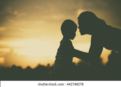 Silhouette of a family comprising mother and children at sunset