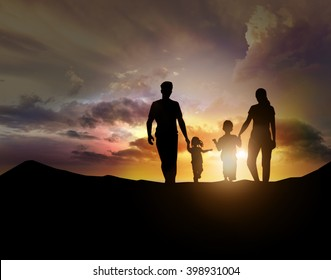 silhouette of family facing the sunset