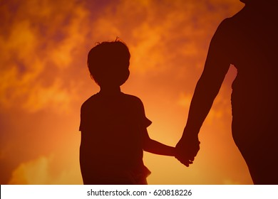Silhouette of family holding hands at sunset sky