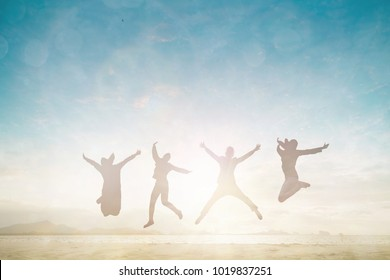 Silhouette family man and woman jump and open arms up on morning beach background good concept for reborn health wellbeing, Financial freedom, mission complete, travel in summer high season.