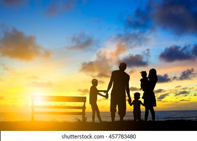 Silhouette family mother father and young son holding hands taking children are excited and delighted over blurred beautiful nature.flare light