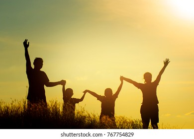 Silhouette of family on the park at the sunset time. People having fun on the field. Concept of friendly family and of summer vacation