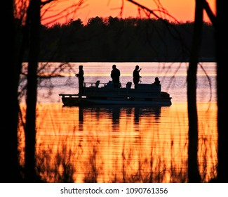 Silhouette of family in pontoon, fishing on Lake Irving at sunset in Bemidji, Minnesota.