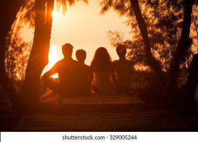Silhouette of a family sitting down and watching the sun setting over the sea. People relaxing at the seaside during holiday and enjoying a beautiful sunset together.