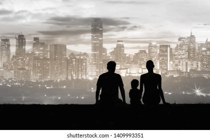 Silhouette of family sitting together looking at city view
