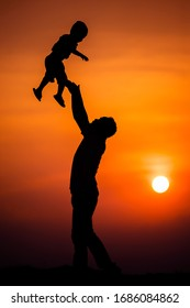 silhouette of the family that the father is playing with the boy happily with the sunset sky