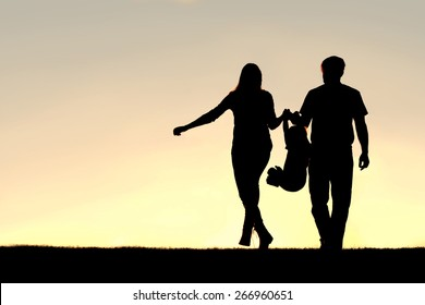 A silhouette of a family of three people, including mother, father, and young child are playing around while walking outside at sunset.