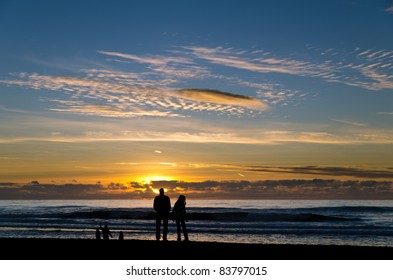 Silhouette of a family watching the sunset at a beach