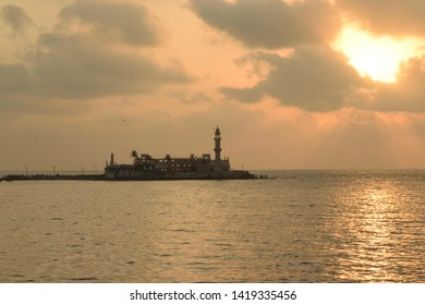 Silhouette of the Famous Haji Ali Dargah on the Arabian seacoast against a sky pattern created by clouds and the setting sun. The shot is taken at Mumbai, India.