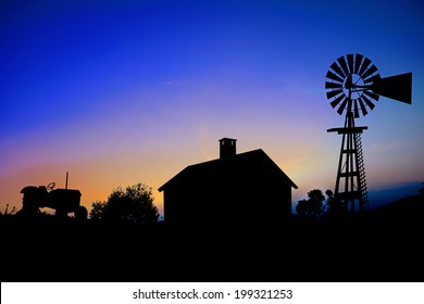 Silhouette of a farm tractor, house and windmill.
