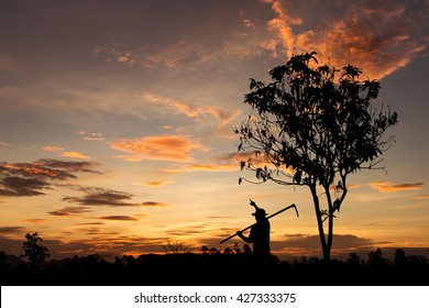 Silhouette of a farmer pointing at orange golden sky, dreaming  background, dark tone image.
