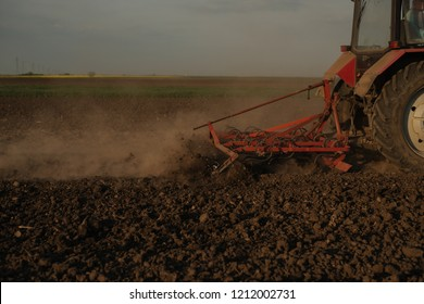 Silhouette of Farmer in tractor preparing land with seedbed cultivator, sunset shot