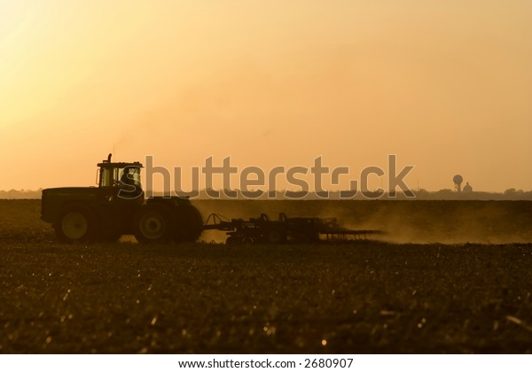 Silhouette of farmer in tractor tilling his land in late autumn after the harvest.  In Logan County near Lincoln, Illinois in the Midwest United States.