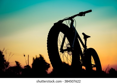 silhouette fat bike at sunset add filter vintage color