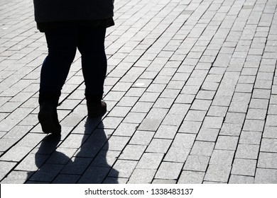 Silhouette of fat woman walking down the street, black shadow on pavement. Thick legs in jeans, concept of overweight, diet, loneliness, dramatic life story
