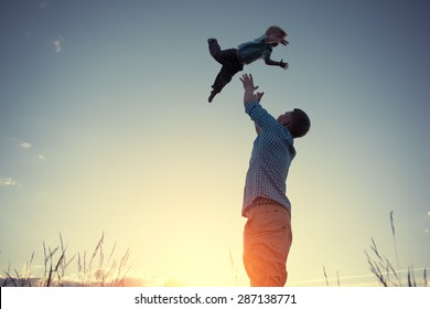 silhouette of father catching his son in the park at sunset (intentional sun glare and vintage color)