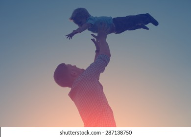 silhouette of father catching and playing with his son in the park in the evening (intentional sun glare and vintage color, lens focus on father)