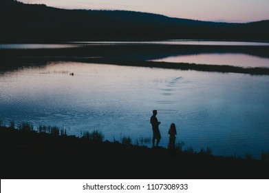Silhouette of father and child skipping rocks at sunset pond background