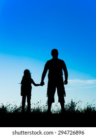 silhouette father and daughter holding hands at sunset.