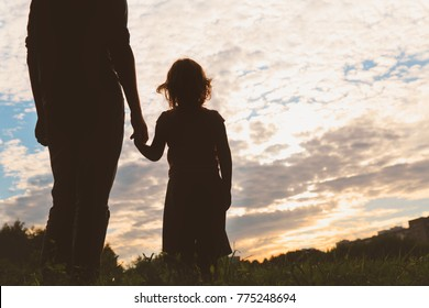 silhouette of father and daughter holding hands at sunset