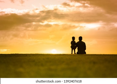Silhouette of father and his little boy watching the sunset.