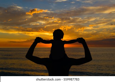 silhouette of father and his small son sitting on dadâ??s shoulders looking at beautiful bright sunset on the ocean