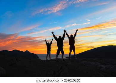 Silhouette of father and his two sons standing on top of a mountain expressing joy with their arms stretched up towards a colorful, vibrant sky at sunset, Sjonfjellet, Norway.