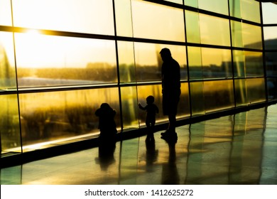 Silhouette of father with kids on airport, family waiting for their flight, sunrise