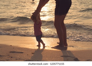 Silhouette of father and little daughter learning to walk at sunset beach. Female infant ten months old. Happy family concept.