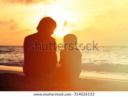 silhouette of father and little son looking at sunset on beach