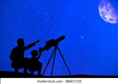 Silhouette of father and son looking moon through a telescope at beautiful night sky