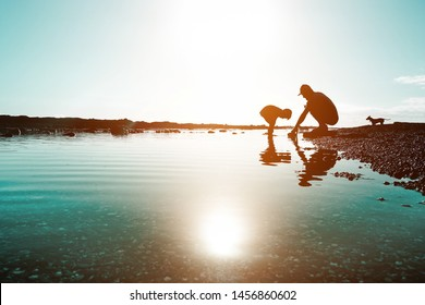 Silhouette of father and son playing on the beach at the sunset time - People having fun on summer vacation with their dog - Love, fatherhood and family