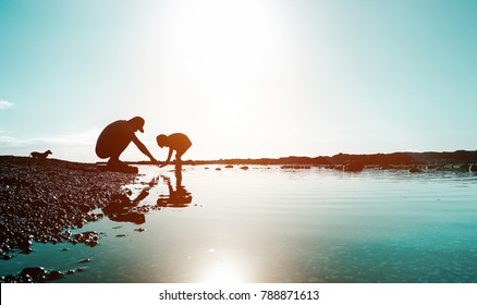 Silhouette of father and son playing on the beach at the sunset time - People having fun on summer vacation with their dog - Love, fatherhood and family concept