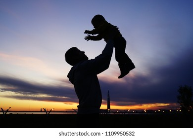 Silhouette of father and son, sunset time, beautiful sky. Sainy-Petersburg