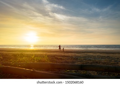 Silhouette of father and son walking at the beach during sunset.