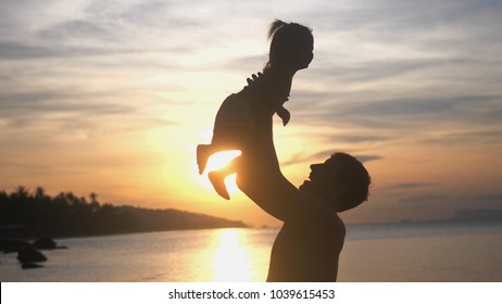 Silhouette of father throwing up his happy daughter in the air at sunset on tropical beach