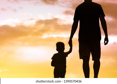 Silhouette of father walking together with little son holding hands facing sunset