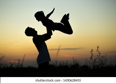 A silhouette of a father who holds his happy daughter and throws up in the air at sunset. family time together