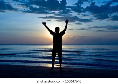 silhouette of feel free and happy man on the beach